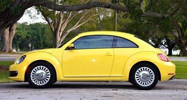 a yellow car standing near road